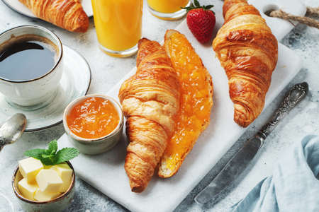 Fresh sweet croissants with butter and orange jam for breakfast. Continental breakfast on a white concrete table