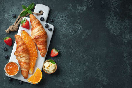 Fresh sweet croissants with butter and orange jam for breakfast. Continental breakfast on a black concrete table. Top view with copy space. Flat lay