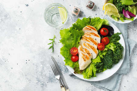Chicken breast fillet and vegetable salad with tomatoes and green leaves on a light background. The concept of healthy food and keto diet. Top view with copy space Фото со стока