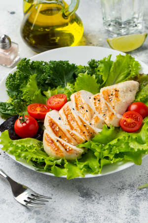 Chicken breast fillet and vegetable salad with tomatoes and green leaves on a light background. The concept of healthy food and keto diet