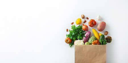 Healthy food background. Healthy vegan vegetarian food in paper bag vegetables and fruits on white, copy space. Shopping food supermarket and clean vegan eating concept