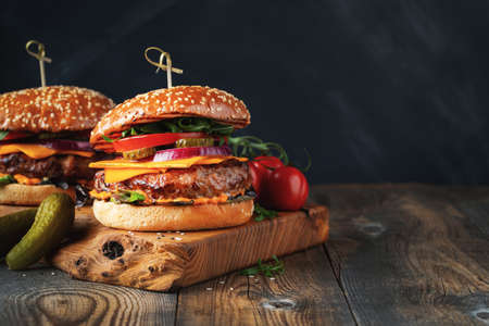 Two delicious homemade burgers of beef, cheese and vegetables on an old wooden table. Fat unhealthy food close-up. With copy space Фото со стока