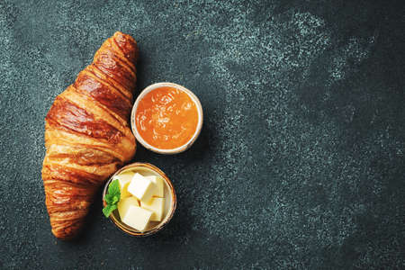 Fresh sweet croissant with butter and orange jam for breakfast. Continental breakfast on a black concrete table. Top view with copy space. Flat lay Фото со стока