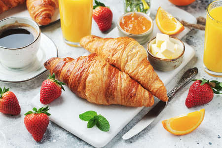 Fresh sweet croissants with butter and orange jam for breakfast. Continental breakfast on a white concrete table.