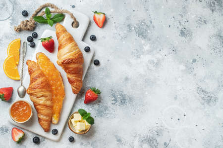Fresh sweet croissants with butter and orange jam for breakfast. Continental breakfast on a white concrete table. Top view with copy space. Flat lay