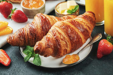 Fresh sweet croissants with butter and orange jam for breakfast. Continental breakfast on a black concrete table. Фото со стока