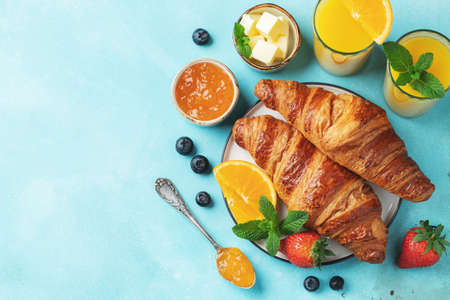 Fresh sweet croissants with butter and orange jam for breakfast. Continental breakfast on a bright concrete table. Top view with copy space. Flat lay