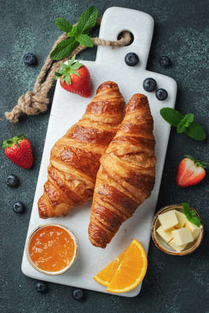 Fresh sweet croissants with butter and orange jam for breakfast. Continental breakfast on a black concrete table. Top view. Flat lay