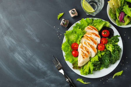Chicken breast fillet and vegetable salad with tomatoes and green leaves on a black background. The concept of healthy food and keto diet. Top view with copy space