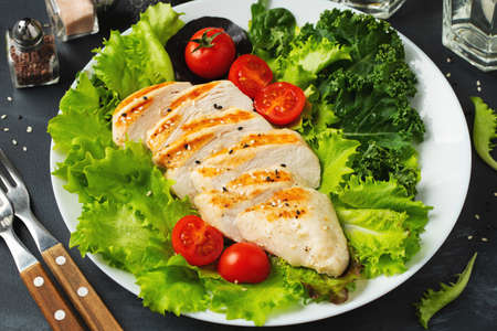 Chicken breast fillet and vegetable salad with tomatoes and green leaves. The concept of healthy food and keto diet Фото со стока