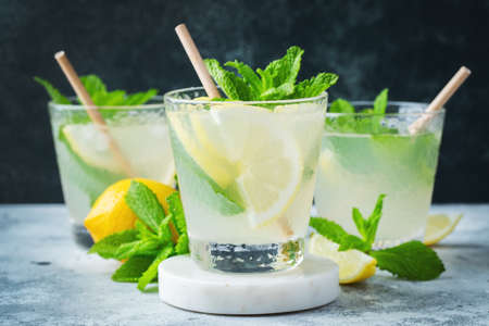Two glass with lemonade or mojito cocktail with lemon and mint, cold refreshing drink or beverage with ice on rustic blue background.