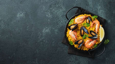 Traditional spanish seafood paella in pan with chickpeas, shrimps, mussels, squid on black concrete background. Top view with copy space.