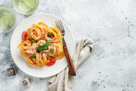Tasty appetizing classic italian tagliatelle pasta with tomato sauce, cheese parmesan and basil on plate on light table. View from above, horizontal. Top view with copy space. Imagens