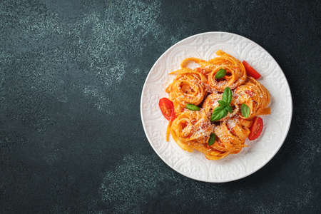 Tasty appetizing classic italian tagliatelle pasta with tomato sauce, cheese parmesan and basil on plate on dark table. View from above, horizontal. Top view with copy space.