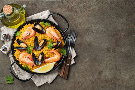 Traditional spanish seafood paella in pan with chickpeas, shrimps, mussels, squid on brown concrete background. Top view with copy space.