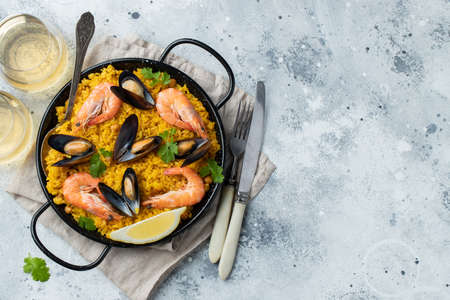 Traditional spanish seafood paella in pan with chickpeas, shrimps, mussels, squid on light gray concrete background. Top view with copy space.