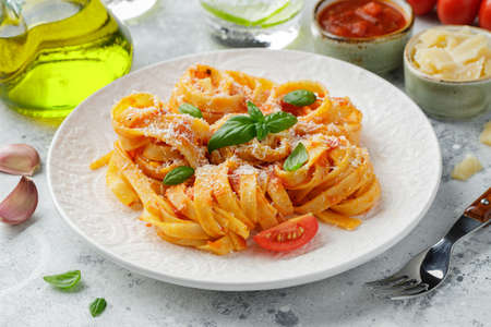 Tasty appetizing classic italian tagliatelle pasta with tomato sauce, cheese parmesan and basil on plate on light table. View from above, horizontal.