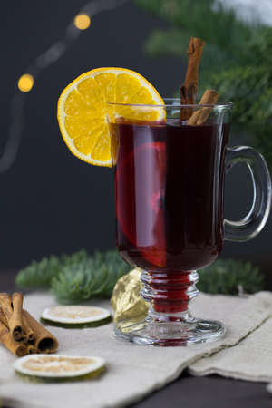 winter treats, a mug of warm wine with an orange, and cookies, ingredients on a wooden brown table. Traditional hot drink for Christmas, in the background Christmas composition. Imagens