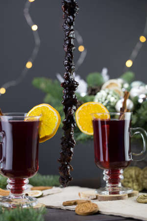 Mugs of warm wine with orange, cookies and cinnamon, dried fruit and spruce branches, Traditional hot drink for Christmas, close-up shot of warm wine