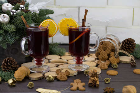 Mugs of warm wine with orange, cookies and cinnamon, dried fruit and spruce branches, hot drink for Christmas.