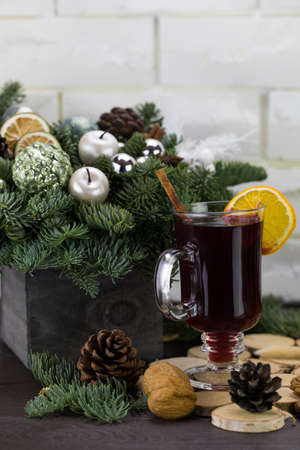 Mugs of warm wine with orange, cookies and cinnamon, hot drink for Christmas, on a wooden stand.