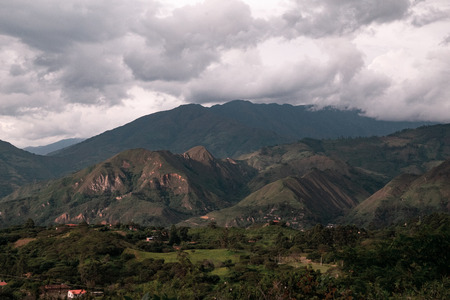 Village in a valley among mountains and clouds