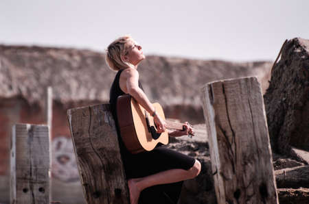 Girl playing guitar on the wooden pillars on the beach on the house background 写真素材