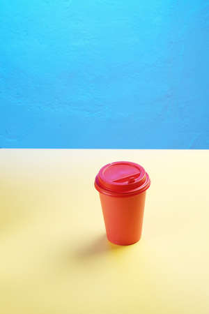 A red coffee plastic mug stands on a yellow table with blue empty space for mock up 写真素材