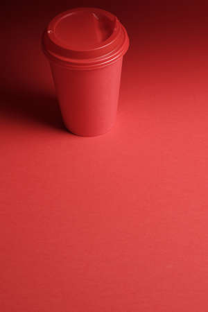 Red plastic coffee mug on a red background with a red lid with empty space for mock up