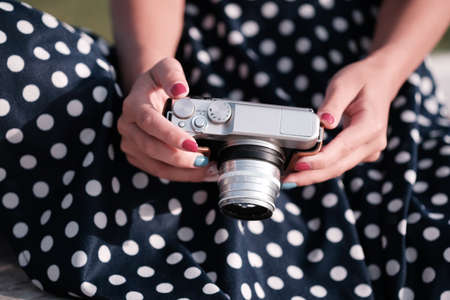 Mirrorless camera like film camera in the hands of a girl in a polka-dot dress