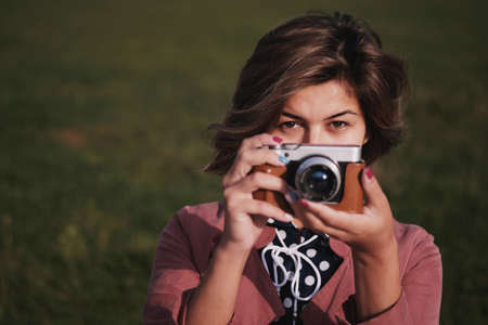 A girl on a green darc background with a mirrorless camera in her hands and looks to the frame with empty space