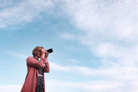 A girl is holding a mirrorless camera against the sky and clouds background 写真素材