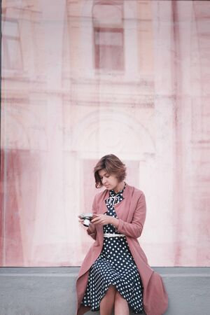 Girl photographer in a pink coat sits on the curb with mirrorless camera in her hands and looks away on a pink background. Waiting girl