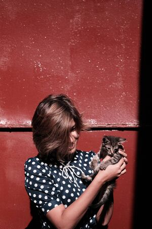 A girl and a cat are looking at each other against the red wall. The kitten sits on the hands of the girl and looks gently to her 写真素材