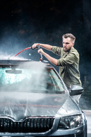 A man with a beard washes a gray car with a high-pressure apparatus at night in a car wash. Expensive advertising photography 免版税图像