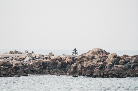 Cyclist rides along a path with large rocks along the sea  ocean with copy empty space 写真素材