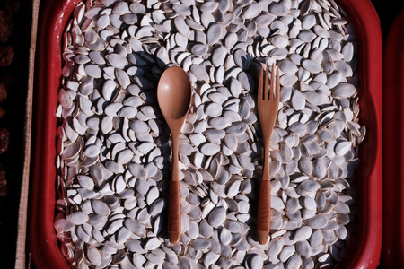 A wooden spoon lies on pumpkin seeds and is filled with them
