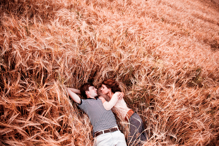 The couple - man and beautiful girl lies on the rye field 写真素材