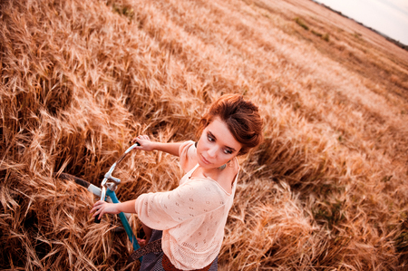 Girl at the wheel of a bicycle against the background of a field in the rye looks at the other side of the frame view from above