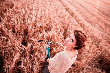 Girl at the wheel of a bicycle against the background of a field in the rye looks at the camera frame of the frame view from above