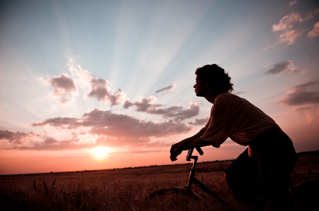 Silhouette of the girl behind the wheel of a bicycle on the background of a sunset in the clouds. Unusual foreshortening