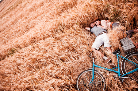 The couple - man,  beautiful girl and bicycle lies on the rye field - view from above