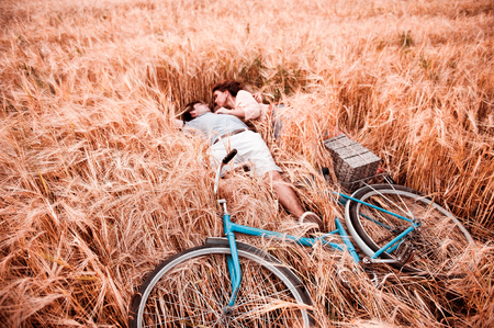 The couple - man,  beautiful girl and bicycle lies on the rye field 写真素材
