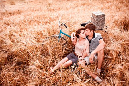 A beautiful girl with a guy is sitting side by side in a rye field next to a bicycle