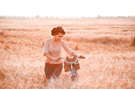 A beautiful girl in a golden rye field romantically comes with a bicycle on which gifts and looking on the bike
