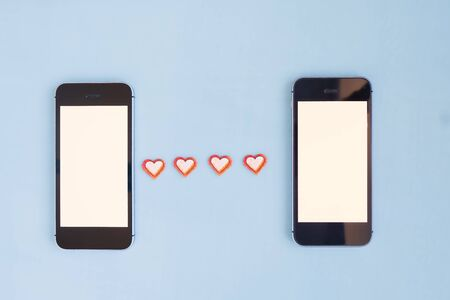 Mock up of two mobile phones between them red cut out paper hearts on a blue background. The concept of communication, flirting between two people