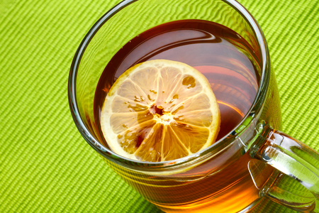 Cup of black tea with lemon on green background.