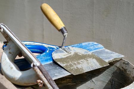 Putty knife and spackling tools on bucket next to grey exterior wall. Stock Photo