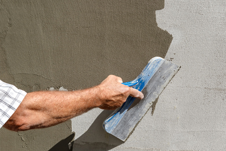 Mans hand applying fresh spackling paste to exterior wall. Stock Photo