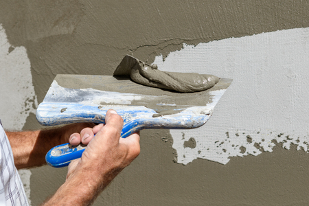 Man applying grey speckling to exterior wall on sunny day.